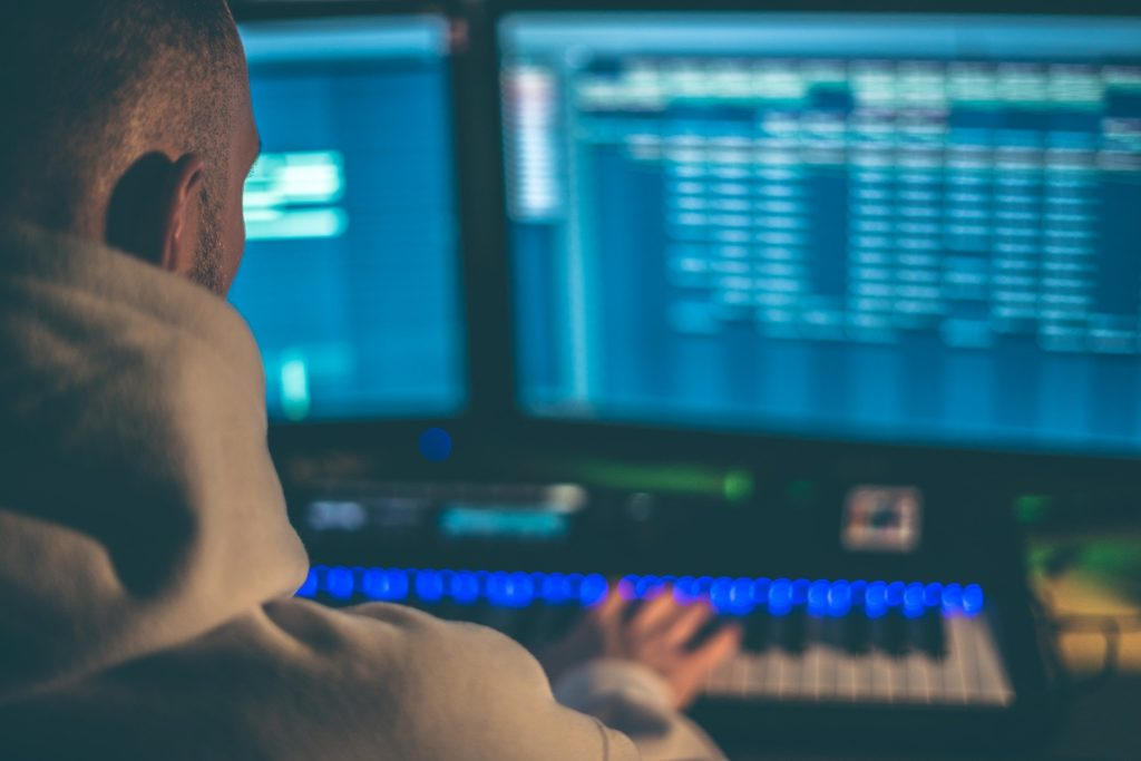 Man at a computer learning how to become a better music producer